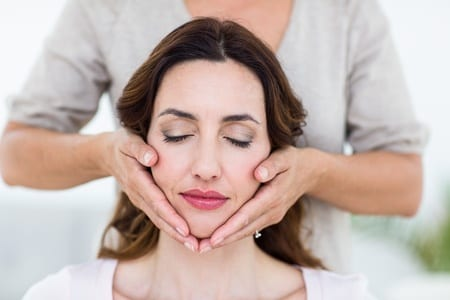 Woman's face with eyes closed during Reiki Massage by Nirvana Wellness Massage